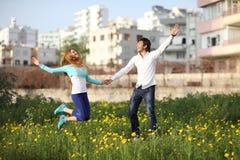 Junge Paare, die in Wiese springen Stockfotos