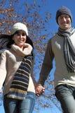 Junge Paare, die in Winterkleidung laufen Stockbilder