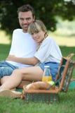 Junge Paare, die Picknick genießen Stockfotos