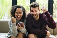 Junge Paare, die zu Hause amerikanischen Fußball aufpassen stockbilder