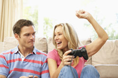 Junge Paare, die zu Hause Computer-Spiel auf Sofa spielen Stockfotografie