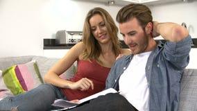Junge Paare, die zu Hause durch persönliche Finanzen schauen stock video