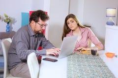 Junge Paare, die zu Hause mit Technologie arbeiten Lizenzfreie Stockfotografie