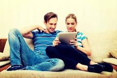 Junge Paare, die zu Hause sitzen und nach etwas auf Tablette suchen lizenzfreie stockfotos