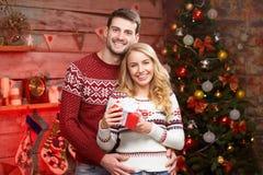 Junge Paare, die zu Hause Weihnachten feiern Stockbild