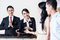 Junge Paare, die zu Hotelempfangsbereich kommen lizenzfreies stockfoto