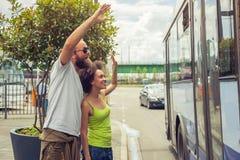 Junge Paare, die zu ihren Freunden auf dem Bus zum Abschied winken Stockbild