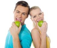 Junge Paare, die zurück zu Rückseite mit grünen Äpfeln aufwerfen stockfotografie