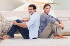 Junge Paare, die zurück zu Rückseite sitzen Stockfotos