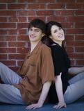 Junge Paare, die zurück zu Rückseite sitzen Lizenzfreie Stockbilder