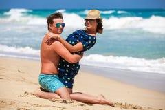 Junge Paare, die zusammen auf einem Sand durch Ozean sitzen Stockbild