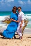 Junge Paare, die zusammen auf einem Sand durch Ozean sitzen Stockfotografie