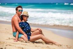 Junge Paare, die zusammen auf einem Sand durch Ozean sitzen Lizenzfreie Stockbilder
