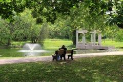 Junge Paare, die zusammen auf Parkbank sitzen Lizenzfreie Stockfotos