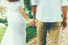 Junge Paare, die zusammen eigenhändig Hand in Sommer-Park, hintere Ansicht gehen lizenzfreies stockfoto