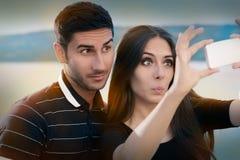 Junge Paare, die zusammen ein lustiges Selfie nehmen Stockbild