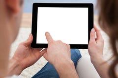 Junge Paare, die zusammen eine Tablette betrachten Stockfotografie