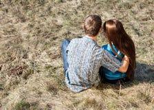 Junge Paare, die zusammen im Park sitzen Stockfotos