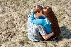 Junge Paare, die zusammen im Park sitzen Lizenzfreies Stockfoto