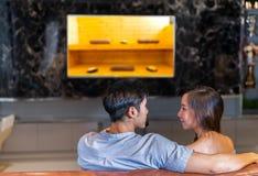 Junge Paare, die zusammen mit Saunabadekurort im Erholungsort fernsehen stockbilder