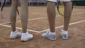Junge Paare, die zusammen nach Tennisspiel am Gericht, aktiver Lebensstil gehen lizenzfreie stockfotos