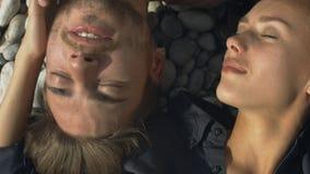 Junge Paare, die zusammen oben auf einem Sand durch Meer, Abschluss liegen stock video