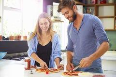 Junge Paare, die zusammen Pizza in der Küche machen Lizenzfreies Stockfoto