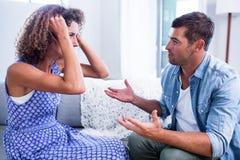 Junge Paare, die zusammen sitzen und nach einem Kampf sich besprechen Lizenzfreie Stockfotografie