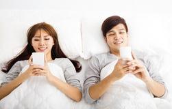 Junge Paare in einem Bett mit intelligenten Telefonen Stockbilder