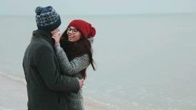 Junge Paare in einem grauen Winter beschichten, Kuss gegen den grauen Himmel und das Meer stock video footage