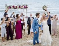 Junge Paare in einer Hochzeitszeremonie am Strand lizenzfreie stockfotos