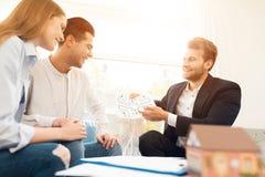 Junge Paare in einer Sitzung mit einem Grundstücksmakler Kerl und Mädchen nehmen einen Vertrag mit kaufendem Eigentum des Grundst stockbild