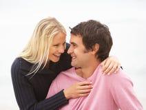 Junge Paare am Feiertag, der auf Winter-Strand sitzt Stockbild