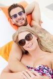 Junge Paare am Feiertag, der durch Swimmingpool sich entspannt Lizenzfreie Stockfotos