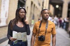 Junge Paare am Feiertag mit einer Karte stockbild