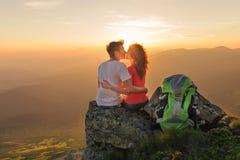 Junge Paare genießen zusammen schönen Sonnenuntergang in den Bergen Lizenzfreie Stockfotos