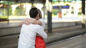 Junge Paare glücklich, sich im Bahnhof wieder zu treffen Mädchen-Läufe, zum ihres Freundes zu treffen stock footage