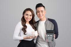 Junge Paare halten rosa Schweinbank und -taschenrechner vorbei an stehend Stockfotografie