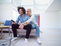 Junge Paare im dem aufpassenden Fernsehen des Sofas stockbilder