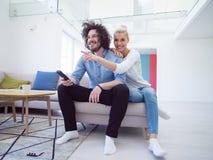 Junge Paare im dem aufpassenden Fernsehen des Sofas stockfotos