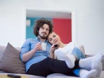 Junge Paare im dem aufpassenden Fernsehen des Sofas lizenzfreie stockfotografie