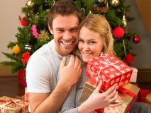 Junge Paare im Haus, das Geschenke austauscht Stockbild