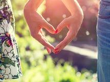 Junge Paare im Liebeshändchenhalten auf dem Sonnenuntergang Lizenzfreie Stockfotografie