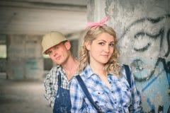 Junge Paare im Overall und in den Sturzhelmen Stockfotos