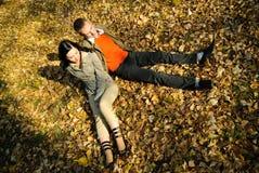 Junge Paare im Park, der auf gelben Blättern sitzt Lizenzfreie Stockbilder