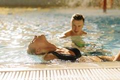 Junge Paare im Pool Mann, der Frau betrachtet Mädchen nehmen ihr vorangehen zurück und gewässert ihrem Haar Lizenzfreie Stockbilder