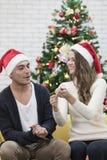 Junge Paare im roten Hut, der auf Sofa zwischen Weihnachtsbäumen sitzt stockfotos
