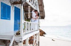 Junge Paare im tropischen Strandhaus Stockfotos