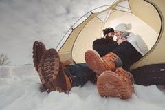 Junge Paare im Zelt während des Winterkampierens Lizenzfreies Stockfoto