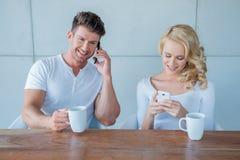 Junge Paare jedes unter Verwendung ihres Handys Stockbild